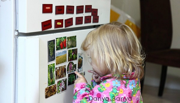 Fruit and vegetable fridge magnets at toddler height provide contextual learning opportunities