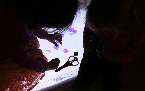 Preschooler and toddler exploring the new light table together