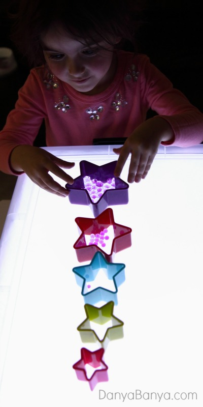 Cookie cutters and water beads on the light table