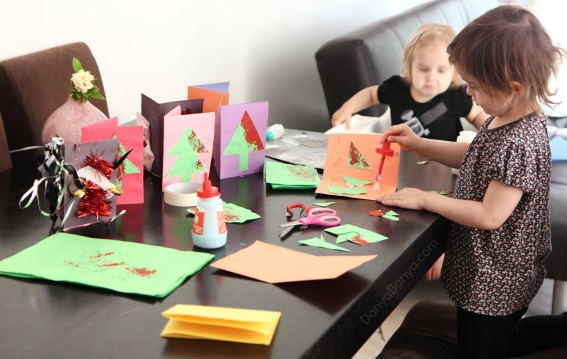 Cutting and gluing kids artwork for homemade Christmas cards that preschoolers can make ~ Danya Banya