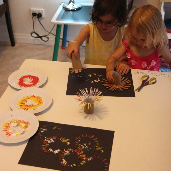 Toddler and preschooler painting fireworks with DIY toilet paper roll stamps