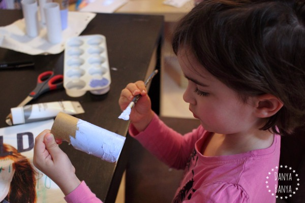 Girl painting a toilet paper roll doll