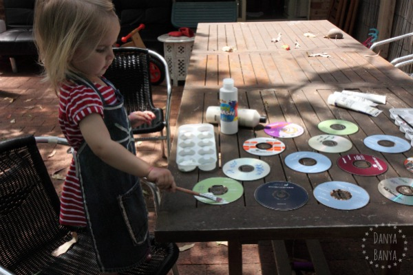 Toddler painting upcycled CDs