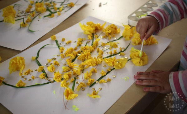 Toddler adding glitter glue (for added sparkle) to the Australian wattle collage