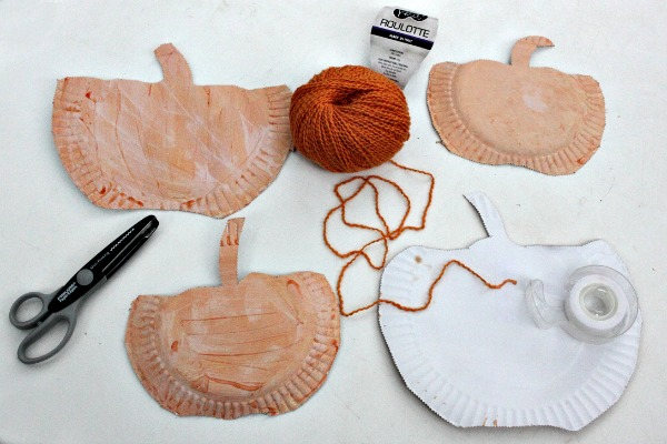 Sticky tape the yarn to the underside of the pumpkin