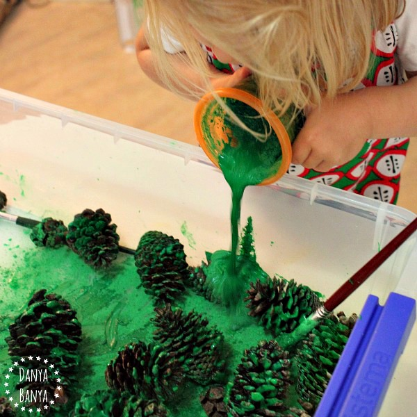 Painting pine cones with green tempera paint