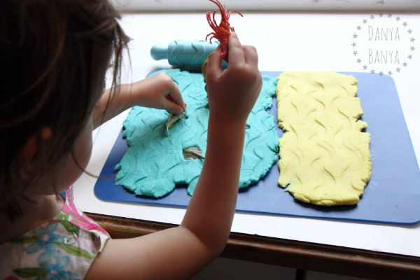 Creating waves in the sea and sand play dough