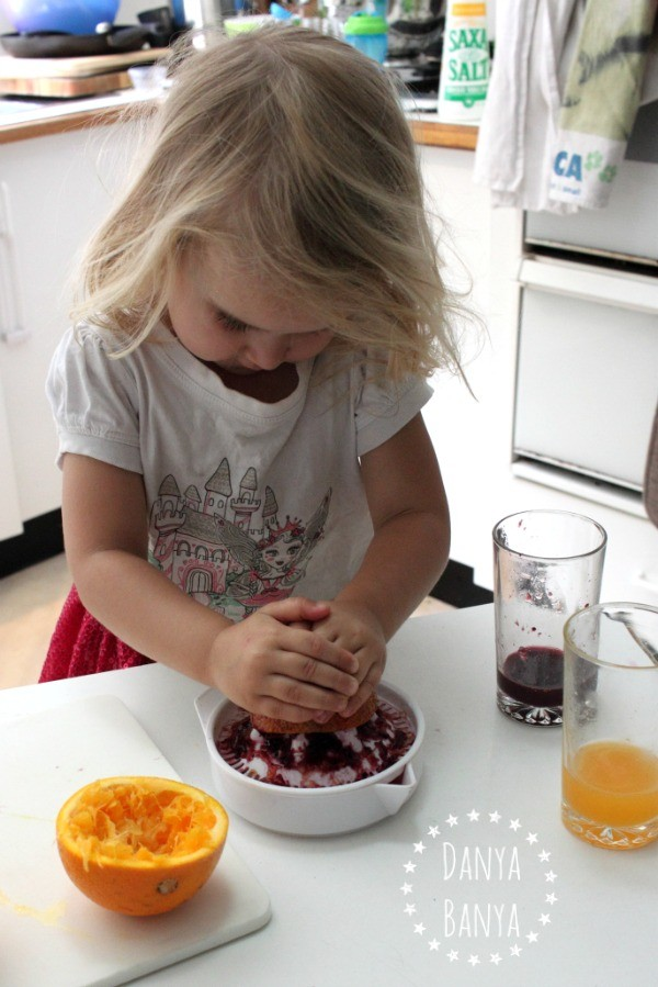 Three year old squeezing fresh blood orange juice